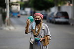 A Palestinian street vendor, mask-clad due to the Covid-19 coronavirus pandemic, sells his merchandise at a street in Gaza City on September 8, 2020. Photo by Osama Baba