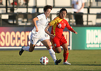 Megan Rapinoe #15 of the USA WNT pushes the ball away from Shanshan Qu #19 of the PRC WNT during an international friendly match at KSU Soccer Stadium, on October 2 2010 in Kennesaw, Georgia. USA won 2-1.