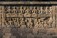 Borobudur, Java, Indonesia.  Bas-relief Stone Carving, North Face.  Scenes from the Buddha's Life, Showing him Seeking Enlightenment.  The top row shows him demonstrating the various mudras (gestures).