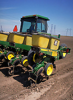 tractor seeding cotton in dirt field. Agribusiness. California.
