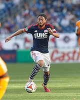 New England Revolution midfielder Lee Nguyen (24) brings the ball forward.  In a Major League Soccer (MLS) match, the New England Revolution (blue/white) defeated Houston Dynamo (orange), 2-0, at Gillette Stadium on April 12, 2014.
