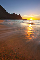 The sun hits the horizon as viewed from Tunnels beach on Kauai's gorgeous north shore.  Mt. Makana (Bali Hai) stands prominently.