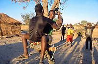 Angola. Cuando Cubango. Mavinga. Late afternoon, man and woman on a swing fixed on a mango tree's bough. © 2002 Didier Ruef