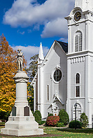 Congregational church clock tower and veterans memorial statue, Manchester, Vermont, USA.
