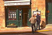 The restaurant Les Epicuriens in the medieval village Saint Emilion, Bordeaux. People tourists reading the  menu outside