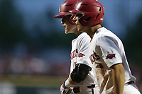 Arkansas catcher Charlie Welch (19) and infielder Robert Moore (1) return to the dugout following a score, Monday, June 7, 2021 in the eighth inning of the NCAA Fayetteville Regional at Baum-Walker Stadium in Fayetteville. Check out nwaonline.com/210608Daily/ for today's photo gallery. <br /> (NWA Democrat-Gazette/Charlie Kaijo)
