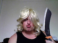 Pictured: A picture taken from Robert Riley's twitter page showing him wearing a wig and holding a long knife.<br />