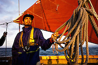 Kaiwi Hamakua-Makue, sunrise, aboard Hokule'a; overnight training sail for worldwide voyage (March 2013); series of tacks from Honolulu out toward Lanai and return to practice setting sails and learning lines. Under the leadership of Captain Bruce Blankenfeld.