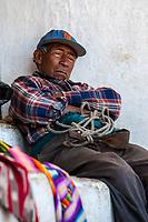 Chichicastenango, Guatemala.  Quiche (Kiche, K'iche') Man Resting Outside Santo Thomas Church, Sunday Morning.