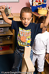 Preschool ages 3-5 boy happy after balancing human figure on block tower vertical