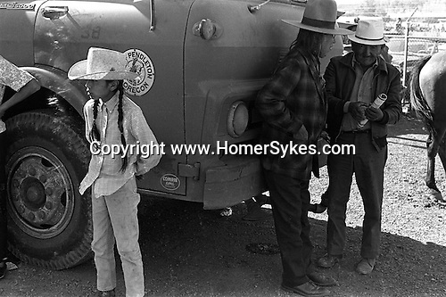A young native American Indian with long pigtails and two elderly men Pendleton Rodeo Oregon USA. 1969