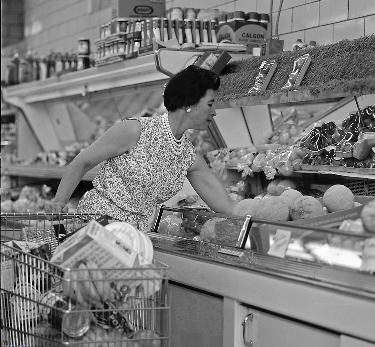 """Bethel Park PA:  View of a woman selecting produce at Bethel Market Grocery Store.  Marjorie Stewart is shopping for produce during an onsite photography assignment for Bethel Market.  Bethel Market was """"the"""" neighborhood grocery store in Bethel Park from the late 1950s through the early 1980s."""