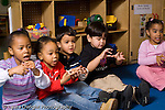 Preschool 3 year olds group at circle time singing song with hand motions horizontal