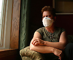 NOT MODEL RELEASED; FOR EDITORIAL USE ONLY... portrait of angry Toronto nurse wearing face mask quarantined at home after exposure to SARS virus