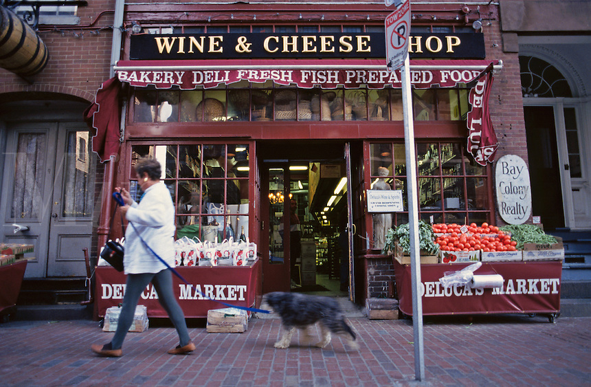 Massachusetts, Boston; Beacon Hill; Woman With Dog Passes Deluca's Italian Market On Charles Stree