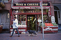 Massachusetts, Boston; Beacon Hill; Woman With Dog Passes Deluca's Italian Market On Charles Stree