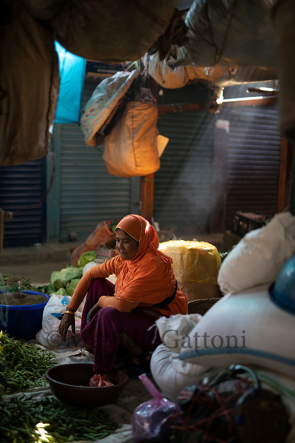 India - Manipur - Imphal - A vegetable seller sits on the floor in her stall. Stalls are very hard to get and can only be passed to married women who belong to the same family.