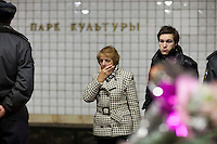 Moscow, Russia, 30/03/2010..A passerby wipes tears from her face as extra police stand guard inside Park Kultury metro station where a female suicide bomber blew herself up the previous day. At least 39 people were killed and 80 injured in the double blasts at Moscow metro stations during the morning rush hour.
