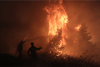 Pictured: Firemen battle with the flames.<br /> Re: A forest fire has been raging in the area of Kalamos, 20 miles east of Athens in Greece. There have been power cuts, country houses burned and children camps evacuated from the area.