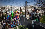 A Palestinian woman holds her child as she stands behind barbed wire fence, photographing Jewish settlers celebrating the Purim holiday, in a parade at the West Bank city of Hebron Sunday March 12 2017. Palestinians can't walk the street during the parade, Purim is a Jewish holiday that commemorates the saving of the Jewish people in ancient Persia , the story is recorded in the Biblical Book of Esther. Photo by Eyal Warshavsky