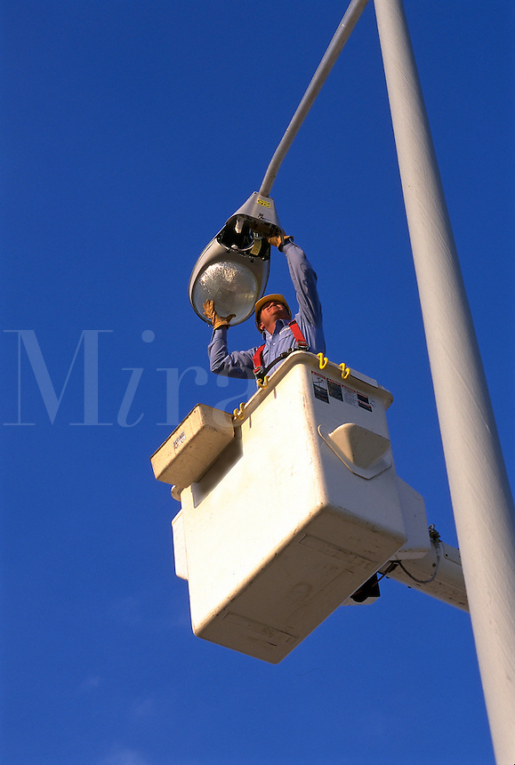 a power company lineman installs street lights for the city from his bucket lift. power company lineman. United States.