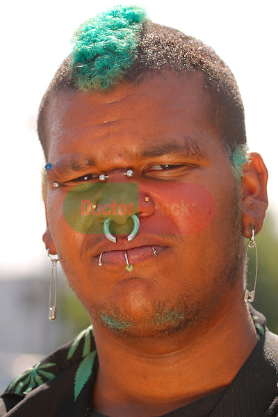 man's face with many piercings, nose ring, studs, lip rings, earrings