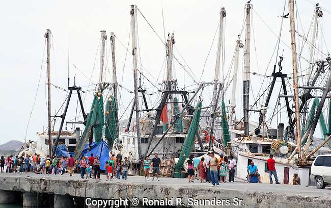 Spectators walk the pier alongside the commercial fishing boats during the Navy Day holiday