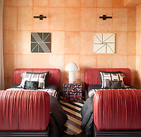 The guest suite features bold, red leather-wrapped padded head and foot boards against a peach dappled wall.
