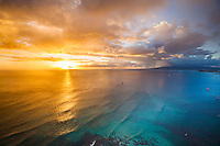 The ocean reflects a colorful sunset with large rainclouds in front of Waikiki, Honolulu, O'ahu.