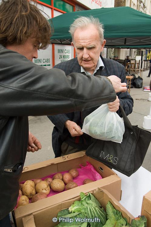 A man shops at a stall at an Farmers' Market in Paddington, London.