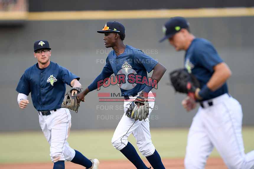Shortstop Ronny Mauricio (2) of the Columbia Fireflies, center, gets a fist bump from Chandler Avant after making a close play in a game against the Rome Braves on Tuesday, June 4, 2019, at Segra Park in Columbia, South Carolina. At right is Brian Sharp. Columbia won, 3-2. (Tom Priddy/Four Seam Images)