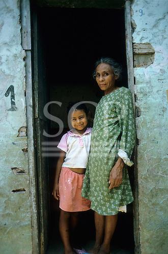 Rio de Janeiro, Brazil. Favela Dona Marta shanty town; women and a girl standing on the doorstep.