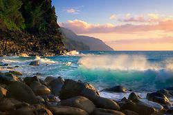 Soft sunset light reflects off the ocean shore looking towards the Na Pali Coast, Hawai'i.
