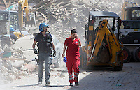 An operator of the Italian Red Cross and a Police officer walk past rubble of collapsed buildings in the village of Amatrice, central Italy, hit by a magnitude 6 earthquake at 3,36 am, 24 August 2016.<br /> Un operatrice della Croce Rossa e un agente di Polizia camminano tra le macerie degli edifici crollati dopo il terremoto che alle 3,36 del mattino ha colpito Amatrice, 24 agosto 2016.<br /> UPDATE IMAGES PRESS/Riccardo De Luca