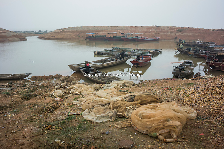 Fishing boats and nets are unattended to during winter in Poyang county at Poyang Lake, Jiangxi Province, December 2014. Poyang Lake, located in the north of Jiangxi Province, is the largest freshwater lake in China. It fluctuates dramatically between wet and dry seasons, from 3,500 square kilometres down to about 200 square kilometres. The lake provides a habitat for half a million migratory birds.
