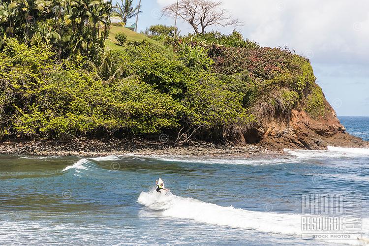 A surfer at Honoli'i Beach Park and Bay, Hilo, Big Island of Hawai'i.