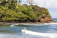 A surfer at Honoli'i Beach Park and Bay, Hilo, Big Island of Hawai'i.