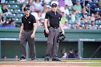 Umpires Tyler Witte, left and Sean Cassidy work a game between the Winston-Salem Dash and the Greenville Drive on Wednesday, June 30, 2021, at Fluor Field at the West End in Greenville, South Carolina. (Tom Priddy/Four Seam Images)