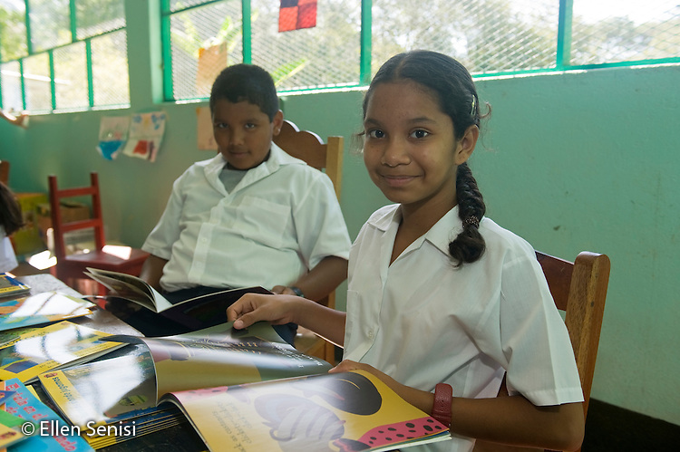 Guanacaste, Costa Rica.Santa Marta School.Two students with new books in the classroom. Students (boy, 9 and girl, 8, Costa Rican) wear their school uniforms..© Ellen B. Senisi
