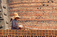 Young girl loading bricks on a truck for transport.The Brick production and Kiln of Vinh Long in the Mekong Delta, Vietnam.