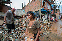 Nepal, Sindhulpalchowk. Earthquake recovery and relief efforts during the summer monsoon rains. Picking up brick by brick, rock by rock. Especially the women carry even more of the workload now.