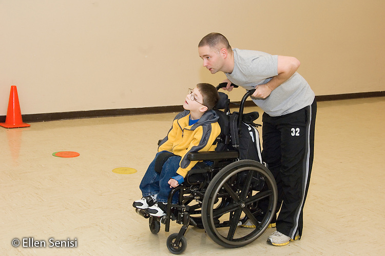 MR / Albany, NY.Langan School at Center for Disability Services .Ungraded private school which serves individuals with multiple disabilities.Physical education teacher ready to move child in wheelchair while playing the field during a modified game of T-ballin Adaptive Physical Education class (APE). Boy: 9, cerebral palsy, limited verbal output with expressive and receptive language delays.MR: Rub1, Pob1.© Ellen B. Senisi