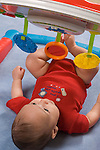 3 month old baby boy  on back closeup interested in hanging toys vertical Hispanic Puerto Rican