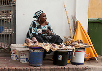 """Senegal, Saint Louis. Street Vendor Selling Peanuts and """"madda"""", or """"maad"""" in Wolof, a fruit from the Casamance area of Senegal, and other areas of the Sahel."""