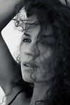 Candid upclose black adn white beauty portrait of a young woman face with expressive brown eyes gazing at the distance and long curly dark hair falling on her beautiful face Image © MaximImages, License at https://www.maximimages.com