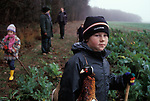 Children rural sport kids at a Game Bird shoot Hampshire England. Young boy collecting shot pheasant hanging around his neck. 2000s