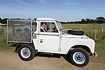 "John Huntley driving the 1974 Land Rover Series 3 88in converted to a winch loading test bed for Land Rover Military 101 winch testing. Dunsfold Collection of Land Rovers Open Day 2011, Dunsfold, Surrey, UK. --- No releases available, but releases may not be necessary for certain uses. Automotive trademarks are the property of the trademark holder, authorization may be needed for some uses. --- Vehicle Information:  Vehicle belongs to the Dunsfold Collection of Land Rovers: Chassis number 90102932A, Registration FXC 863L, Engine 4-cyl petrol 2.25L, Gearbox 4-speed. --- Vehicle History: This white Series 3 88in started life as  motor show car in 1974 with evidence of a styling feature of painting the wheel centers a different colour. After that the rear body was removed and this massive P.T.O. hydraulic which fitted, with a safety cage around it. The use is believed to have been a device for the installation of Land Rover 101 winch cables, probably witch putting a heavy load on the cable for tight spooling and for testing safety features of the 101 winch. The ""Birdcage"", as called at Solihull is still on it's original Dunlop tyres."