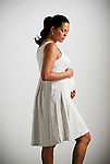 Pregnant Hispanic woman, hands on stomach