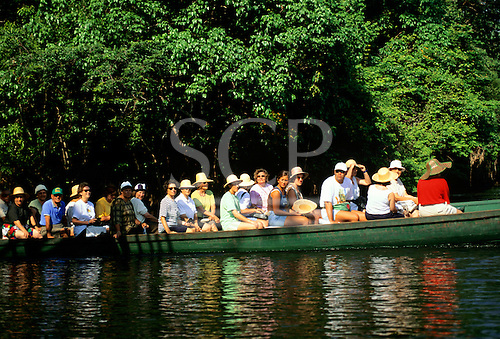 Amazonas State, Brazil. Group of tourists in an open boat on guided tour in the Amazon rainforest; Anavilhanas Archipelago.