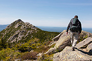 A hiker on Middle Sister Trail with Mount Chocorua in the background in the White Mountains, New Hampshire USA